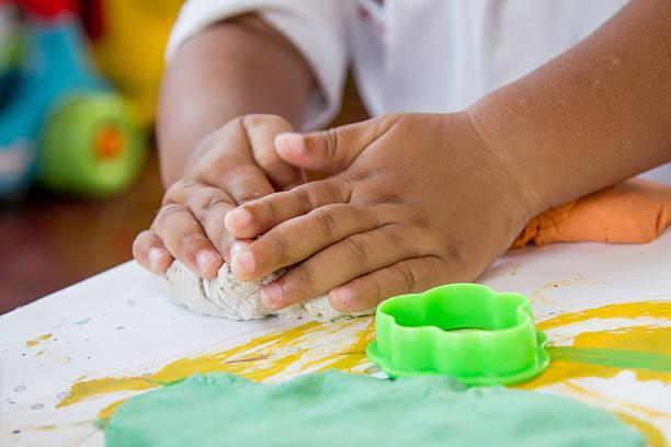 kind hand spielen mit sand spielen doh - knete spiele stock-fotos und bilder