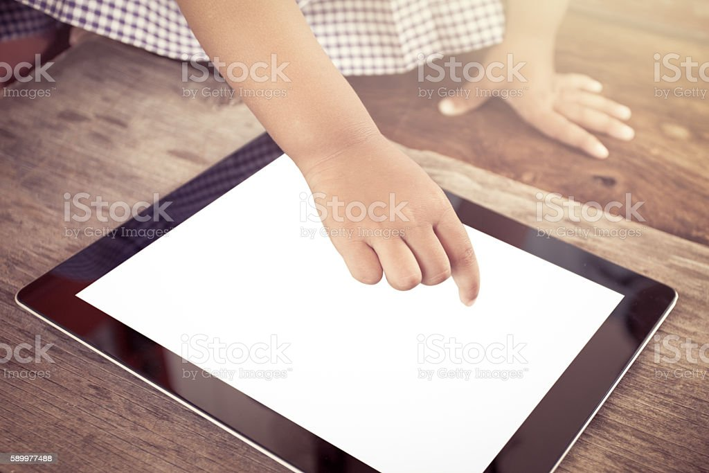 Child hand pointing smart phone,tablet for playing and education stock photo