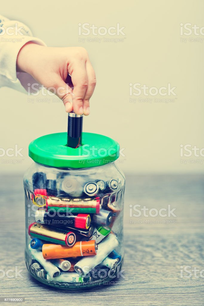 Child hand putting collecting used batteries stock photo