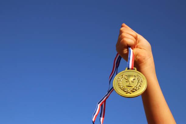child hand raised, holding gold medal against sky. education, success, achievement, award and victory concept. - medal zdjęcia i obrazy z banku zdjęć