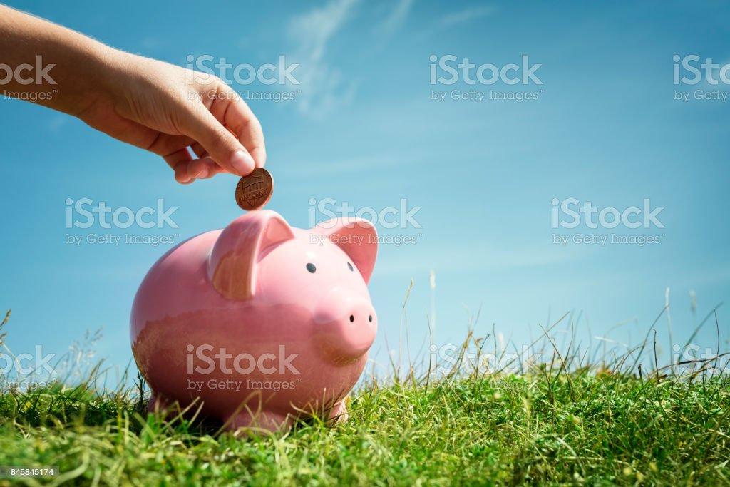 Child hand saving money in piggy bank stock photo