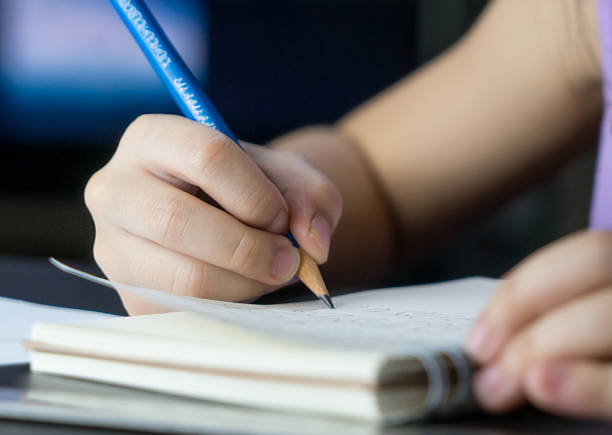 Child hand using pencil to practice writing on a book. - foto de stock