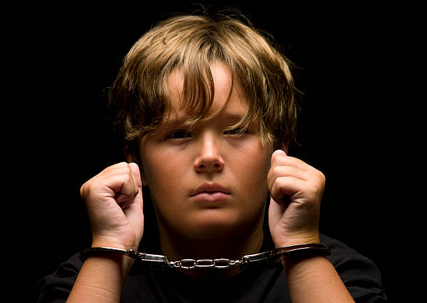 child handcuffed - boy handcuffs stock pictures, royalty-free photos & images