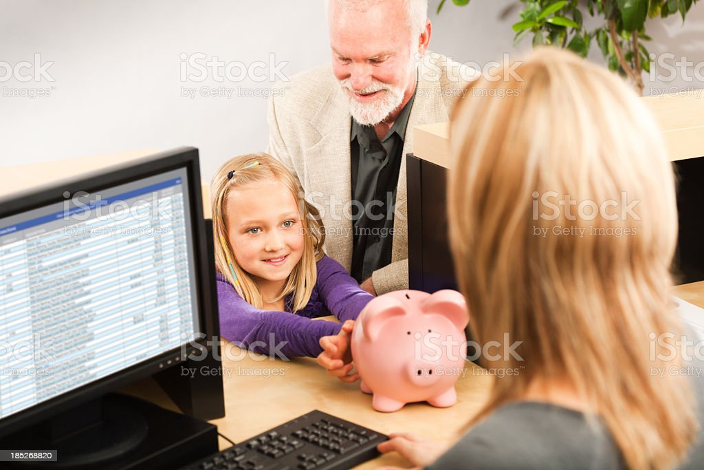 Child Handing Coin Piggy Bank, Opening Bank Account with Teller stock photo