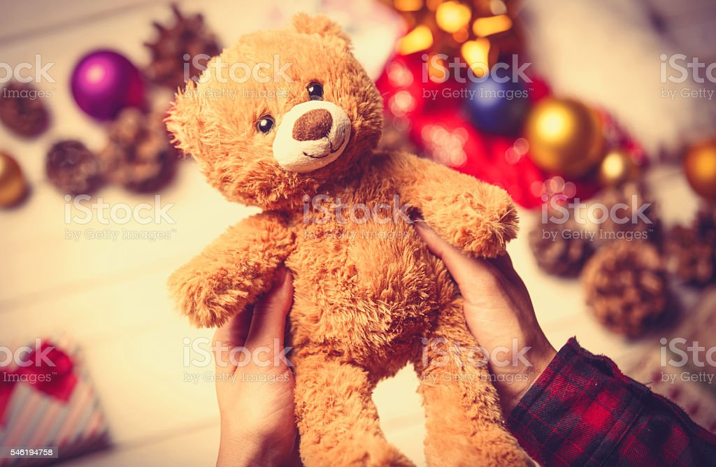 child hands holding a teddy bear stock photo
