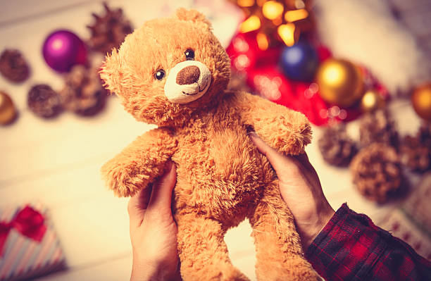 child hands holding a teddy bear photo of the child  hands holding cute teddy bear on the christmas decorations background christmas teddy bear stock pictures, royalty-free photos & images