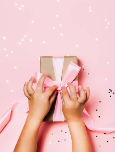 kind die hände halten schöne geschenk-box auf rosa hintergrund - kinder verpackung stock-fotos und bilder