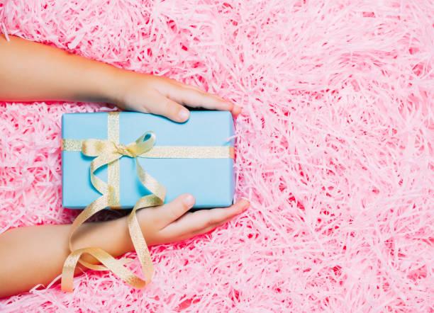 kind die hände halten weihnachts-geschenk-box auf festliche rosa hintergrund. ansicht von oben flach legen. - eco bastelarbeiten stock-fotos und bilder