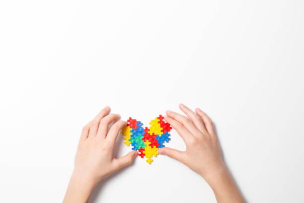 Kinderhände halten buntes Herz auf weißem Hintergrund. Weltautismus-Bewusstseinskonzept – Foto