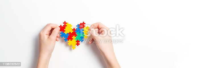 istock Child hands holding colorful heart on white background. World autism awareness day concept 1138232522