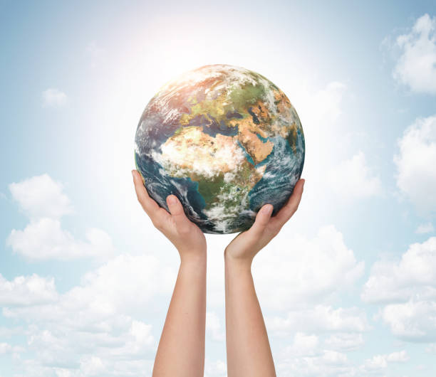 Child hands holding planet earth stock photo