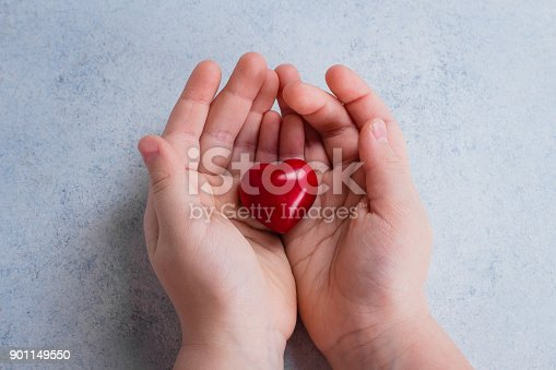 823097608istockphoto Child hands holding red heart. Card for Valentines day. World heart day, world health day, healthcare, donate and family insurance concept. Blue Background 901149550