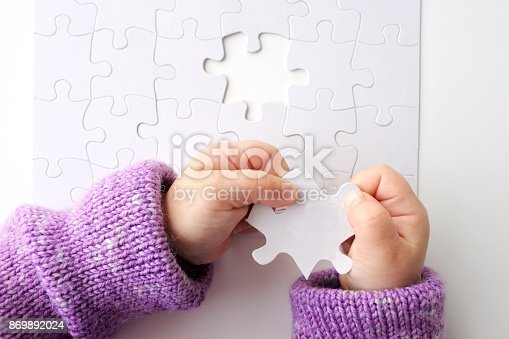 istock Child hands holds the last puzzle piece of a Jigsaw puzzle 869892024