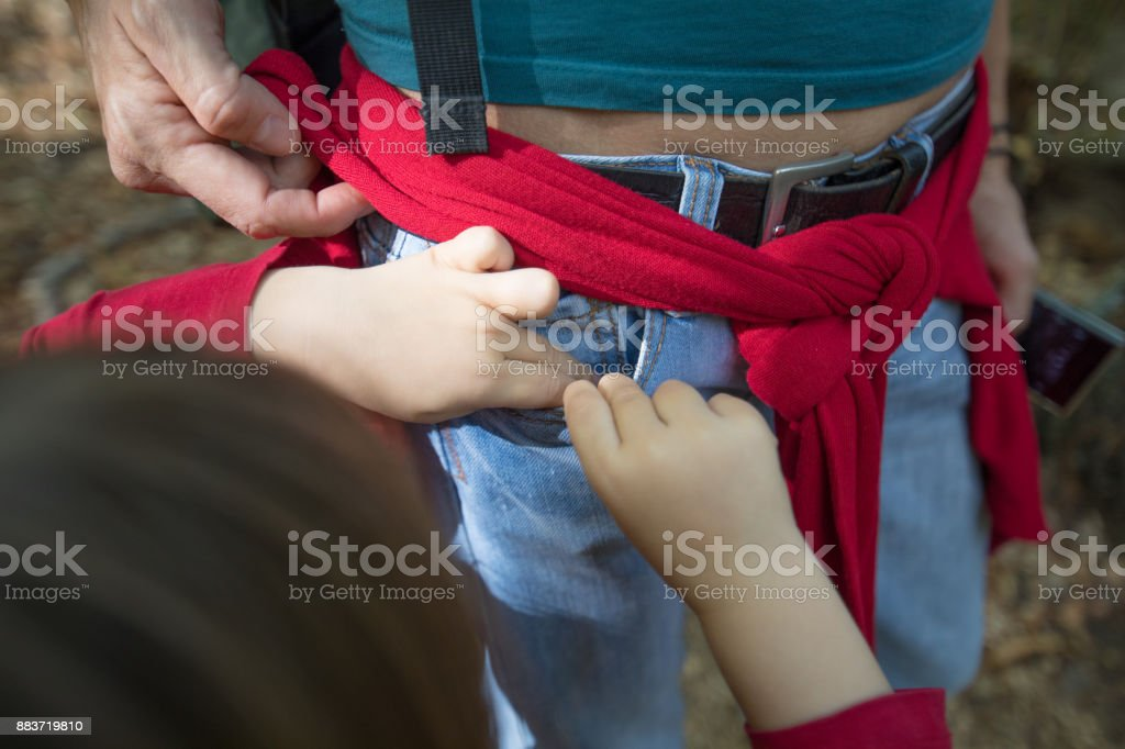 child hands in pocket of blue jeans of woman stock photo