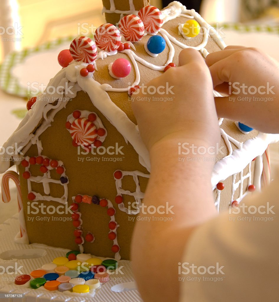 Child Hands Making Christmas Gingerbread Cookie House, Sweet Holiday Food royalty-free stock photo