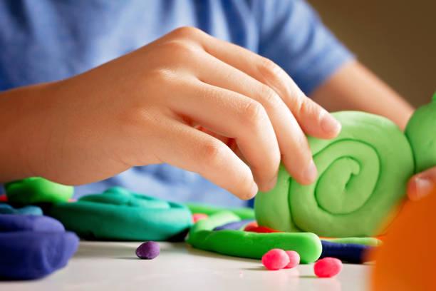 kind die hände machen spielzeugfigur mit modelliermasse oder plastilin - kindergarten workshop stock-fotos und bilder