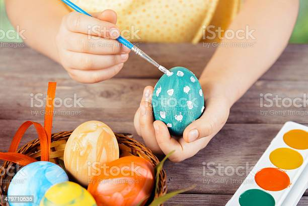 Child hands paint egg for Easter on a wooden table