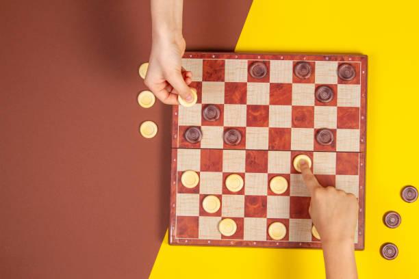 Kinderblätter, die auf dem Brettspiel des Checks über gelben und blauen Hintergrund, der oberen Ansicht, die Schachspieler spielen – Foto