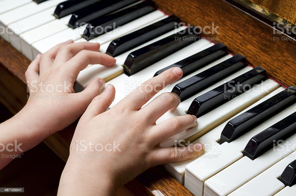 Child hands playing piano stock photo