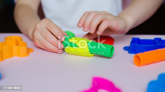 926151996 istock photo Child hands playing with colorful clay. Homemade plastiline. Girl molding modeling clay. Homemade clay. Child playing and creating from play dough. 1216819650