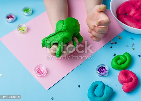 926151996 istock photo Child hands playing with colorful clay. Homemade plastiline. Plasticine. play dough. Girl molding modeling clay. Homemade clay. 1216806129