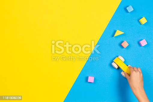 667590810 istock photo Child hands playing with wooden toy car and colourful building blocks on blue and yellow background, top view 1181906226