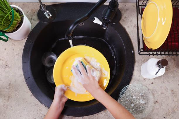 kind die hände waschen gelbe platten bei der küchenspüle - wasch oder spülbecken stock-fotos und bilder