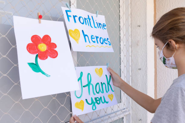 Child hanging positive messages to frontline heroes working during Coronavirus (COVID-19) quarantine hanging on the safety net of a house Positive messages to frontline heroes working during Coronavirus (COVID-19) quarantine hanging on the safety net of a house. heroes stock pictures, royalty-free photos & images