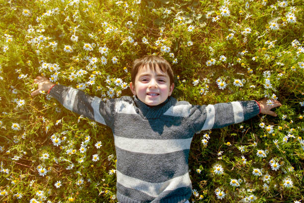 Kind glücklich unter Gänseblümchen – Foto