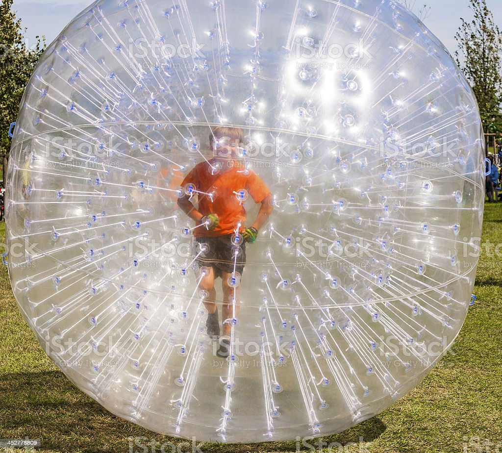 child has fun in the Zorbing Ball stock photo