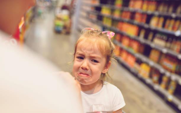 Kind mit Arguement mit Mutter auf Candy Bar – Foto