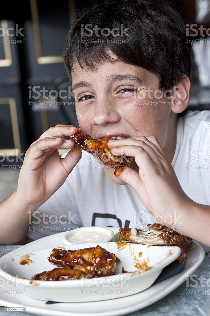 child having buffalo wings stock photo