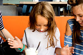 Child having fresh shake. Older sister laughs at younger because of messy