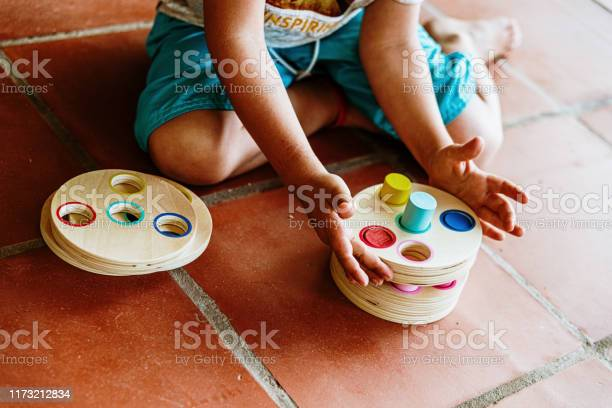 Child having fun with an educational wooden game to fit cylinders picture id1173212834?b=1&k=6&m=1173212834&s=612x612&h=k04eisnfzabtrxgskmyxwdhspg dkbb9fcnr9bagsie=