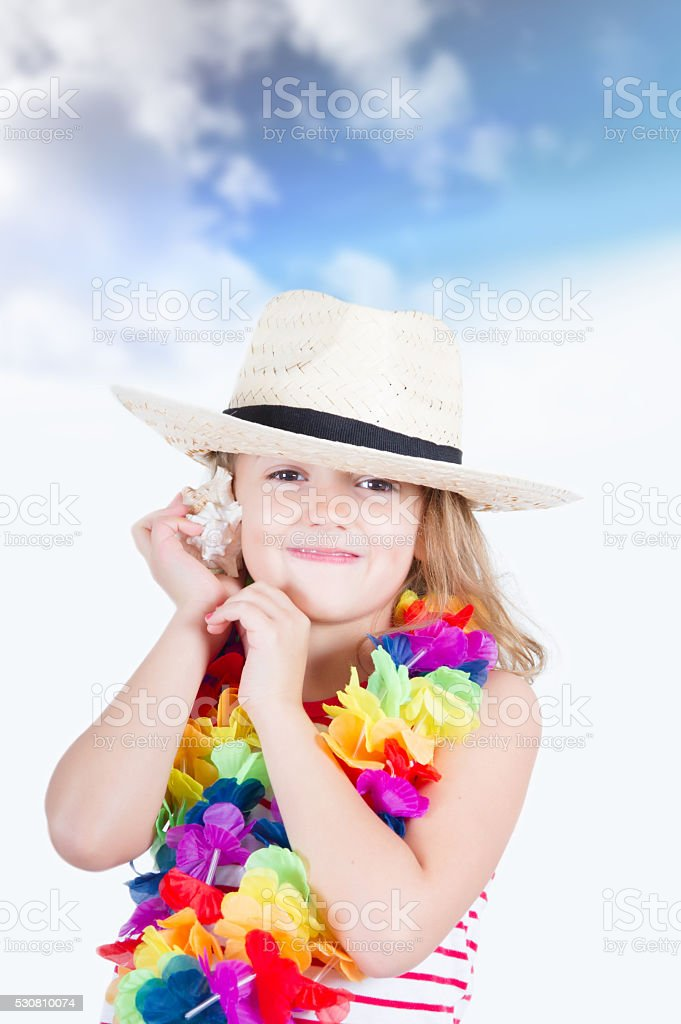 child hears the sound of the sea with shell stock photo
