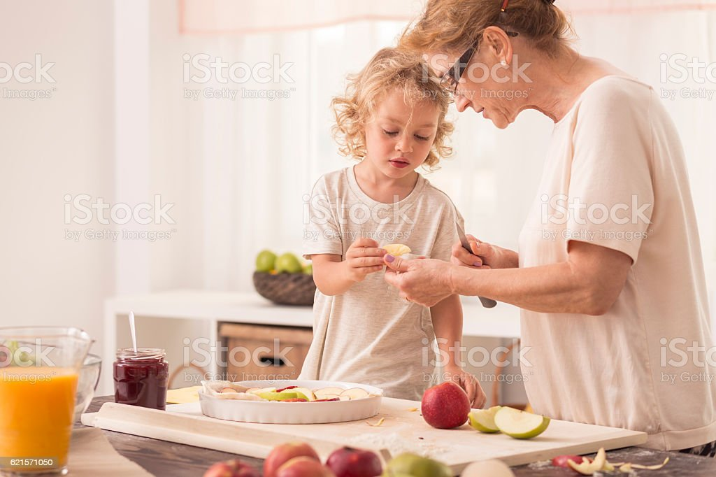 Child helping grandmother with baking photo libre de droits