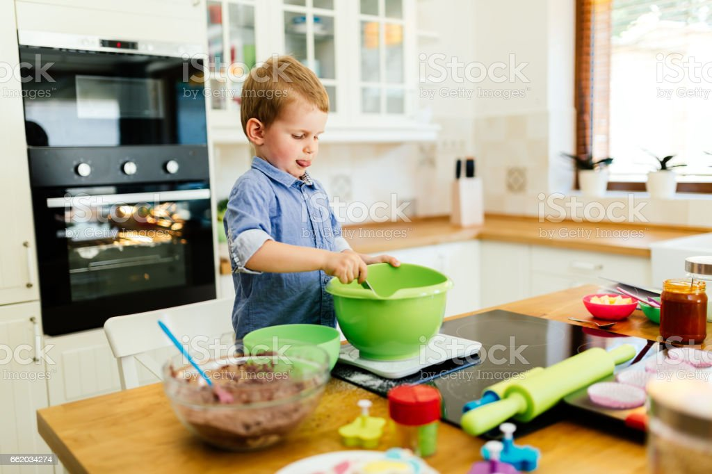 Child helping mother make cookies as a professional chef royalty-free stock photo