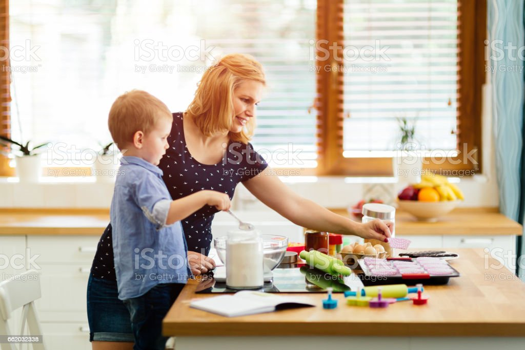 Child helping mother make cookies in modern kitchen royalty-free stock photo
