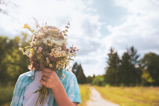 Little child hidden behind a bouquet of wildflowers  on a sunny day.