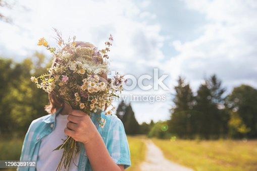 istock Child hidden behind a bouquet of wildflowers 1296389192