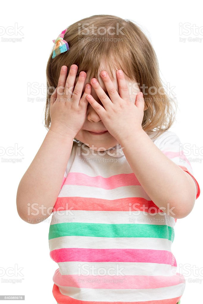 child hiding face by hands stock photo