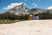 Brave and strong child embarks on a 7 miles hike up to Cathedral Peak in Tuolumne Meadows in Yosemite Valley National Park in California. Beautiful landscape with child exploring, running and playing.