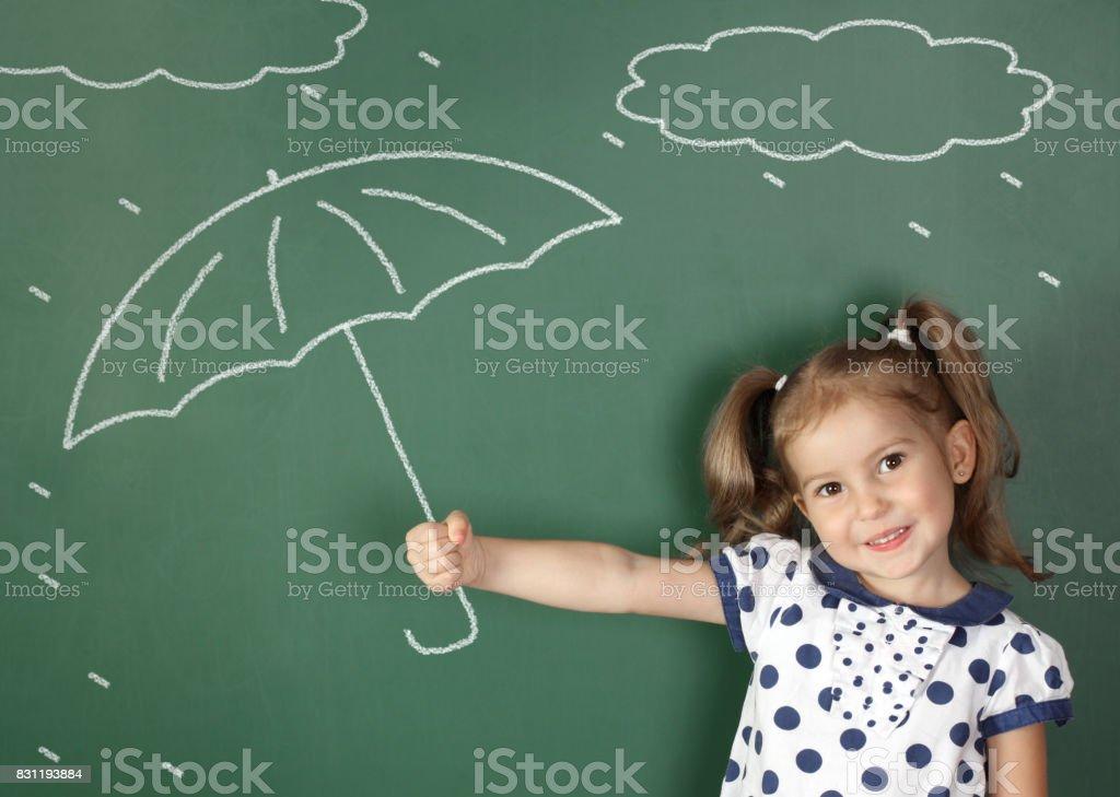 child hold umbrella near school blackboard, weather concept stock photo