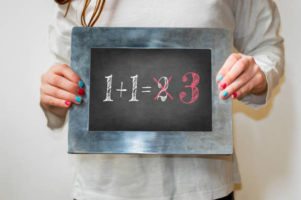 Child holding a blackboard with the text 1+1=3 Child holding a blackboard with the text 1+1=3 number 1 stock pictures, royalty-free photos & images