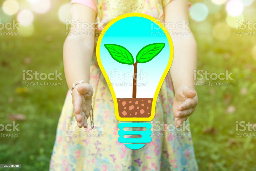 Child holding a bulb with a plant growing inside as 'green thinking' concept  on a sunny day stock photo