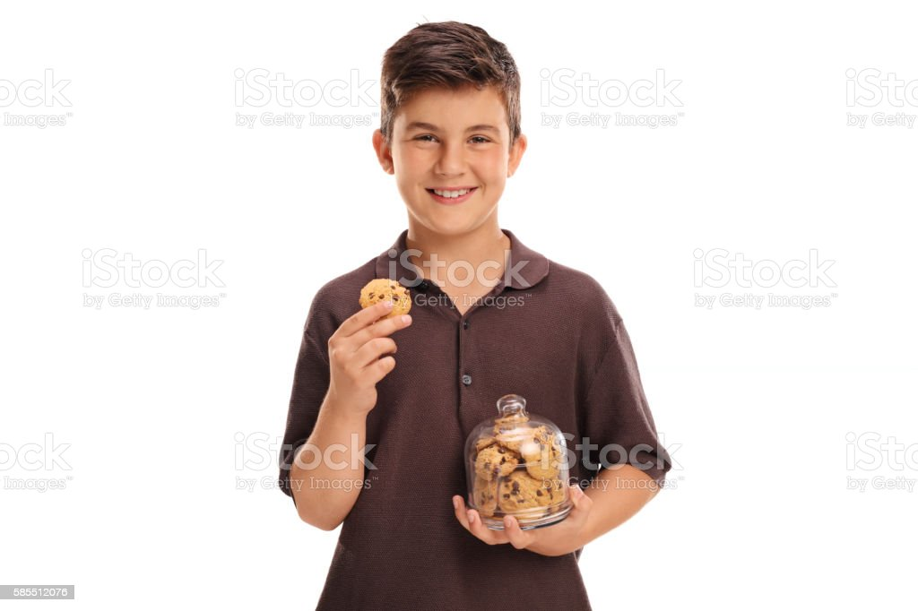 Child holding a cookie and a jar stock photo