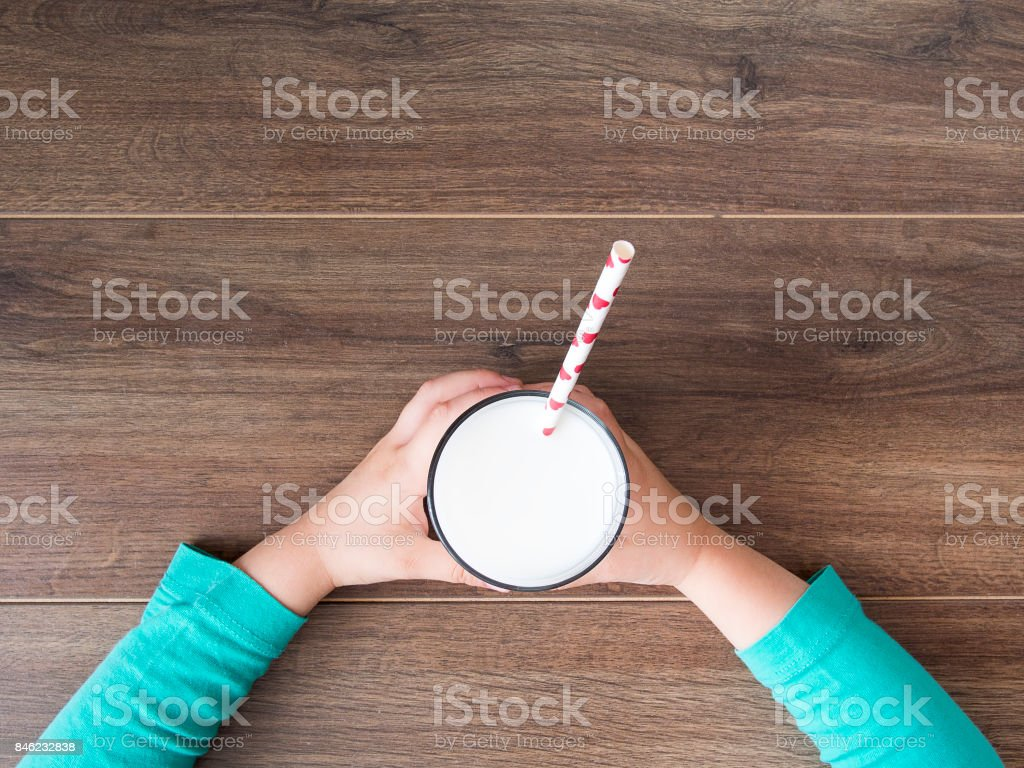 Child holding a glass of milk on dark rustic table stock photo