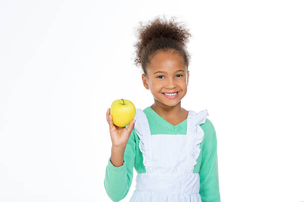 child holding a yellow apple stock photo