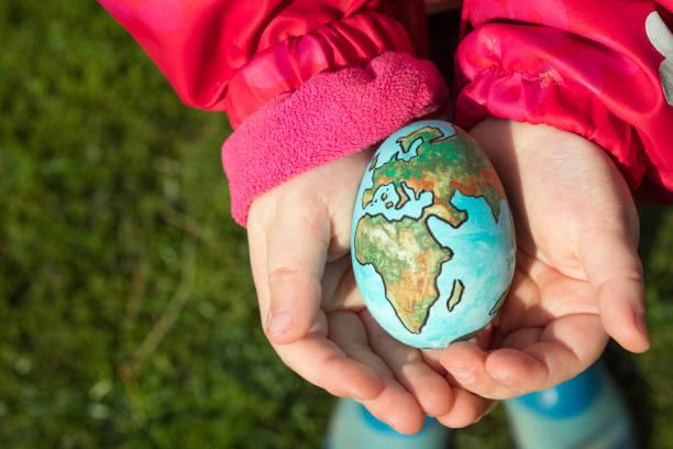 kind hält ein ei mit planetenerde an einem sonnigen tag im freien gemalt - schöne osterbilder stock-fotos und bilder
