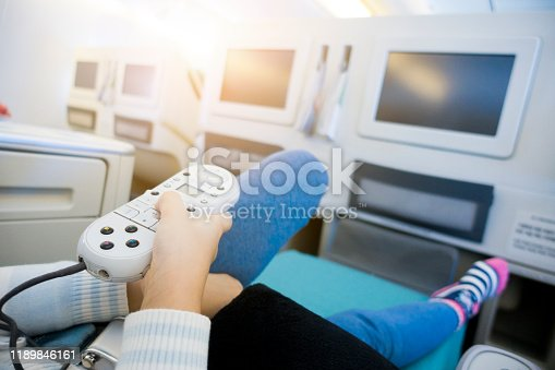 Child Holding an On-flight Entertainment System Remote Control Sitting in Airplane Business Class Cabin.